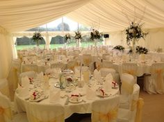 A fully dressed marquee with gold theme, and a spash of red in the flowers