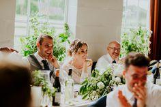 The wedding party enjoying the speeches in Wytham Village Hall, Oxfordshire. Photo by Benjamin Stuart Photography #weddingphotography #speeches #light #wytham #ukwedding #villagehallwedding #flowers #smile