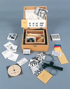 Fluxus Collective's 'Flux Year Box 2' from 1967/1968. Five-compartment wooded box contains the following works: George Maciunas-designed monogram cards for: Eric Andersen, George Brecht, John Cavanaugh, Fred Liberman, George Maciunas, Claes Oldenburg, Yoko Ono, James Vanderbeek, Ben Vautier, Robert  Watts, and unknown (woman's breast); 20 8mm film loops by various artists; film loop viewer with instructions; George Brecht,  Cloud Scissors, Place one card in each of the Five Places Exercise…