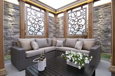 """This inviting, private space transitions down to the ground from a high back door and features a large, beautiful lounge.  We used stone paneling, LED light accents, and cut metal screens for the privacy screens around the lounge. From """"Decked Out"""" episode """"The Triangle Deck"""".  Deck design by Paul Lafrance Design."""