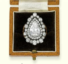 A GEORGE III DIAMOND RING   The pear-shaped diamond weighing approximately 3.00 carats within an old-cut diamond border and surround to the bifurcated shoulders, mounted in silver and gold, early 19th century, in leather case