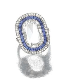 Sapphire and diamond ring, of target design, centering on a cushion shaped diamond bordered by French cut sapphires and millegrain set circular cut diamonds, mounted in platinum. Undated but certainly 20th century