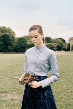 Model reads during Field Day. Photographer Letty Schmiterlow heads into London's green spaces with a troupe of the finest new faces around, styled to '40s perfection. TOPSHOT new season zine, 2013. Light blue button up shirt. Light and dark blue camouflage pattern skirt.