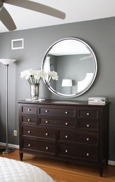 Beautiful master bedroom dresser, wall color, mirror, and mercury glass with white flowers. We even have that white quilt on the bed. I would go for a darker wood floor and add a substantial crown molding.