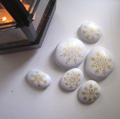 White-painted rocks with golden snowflake designs.