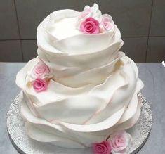 La repostera hace una tarta de fondant utilizando una gran cantidad de flores de diferentes colores rosados ...