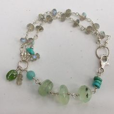 Gemstone and sterling silver bracelet. A double strand of small but highly colored faceted labradorite roundels links to a group of smooth prehnite and turquoise beads. Tiny labradorite, turquoise and