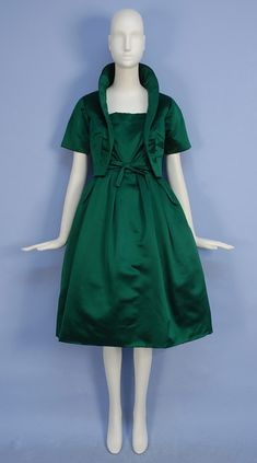CHRISTIAN DIOR SILK DRESS and JACKET SET, 1950's. Sleeveless emerald green satin with square neckline, fitted bodice with self bow at waist, full skirt with large pleats over crinoline, matching short sleeve jacket with shawl collar. New York label. Front 2
