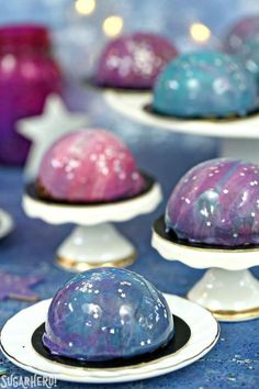 Galaxy Mousse Cakes - mini chocolate mousse cakes on a brownie, with a gorgeous galaxy mirror glaze on top! | From SugarHero.com