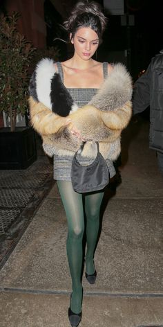 Kendall Jenner took her plaid dress and fur coat to the next level by adding a pair of green tights. All she needed were dainty black heels to finish off the winning outfit. #kendalljenneroutfits