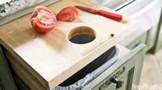In a Houston, Texas, kitchen designed by Michele Allman, a pull-out cutting board has a hole, which makes it easy to brush the scraps straight into the trash bin just below.   - HouseBeautiful.com