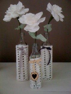 Gehaakte flessen met rozen gemaakt van koffiefilterzakjes