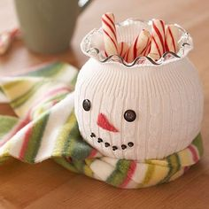 Get circular jar, cover with sock or other white material that stretches,then cover jar.. 2 buttons for eyes, then glue to the sock ... cut triangular felt out of yellow,red or orange,glue under eyes, get smaller beads for the mouth.glue those, too- now you have a happy winter snowman