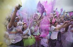 Some of the over 6,000 participants in the Color Run 5 kilometers, throw colored powder and celebrate upon crossing the finish in Susono, at the foot of Mt. Fuji, southwest of Tokyo, Saturday, Sept. 6, 2014. (AP Photo/Eugene Hoshiko)