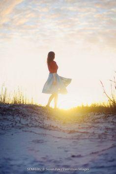 Susan Fox WOMAN WALKING ON SAND DUNE AT SUNSET Women