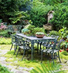 Destination escape: Surrounded by lush plantings, a table sits on pavers almost overgrown with greenery. More beautiful yards: http://www.midwestliving.com/garden/ideas/30-beautiful-backyards/