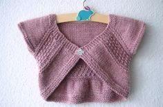 """Adorable seamless shrug that knits up in no time and uses very little yarn… Features a fun and easy textured pattern. Both the heartwarmer style and the textured stitch made me think of the """"entrechat,"""" a ballet jump where the legs cross each other mid-air in a flutter. Sizes available: 0-3mo (3-6mo, 6-12mo, 12-18mo // 2-3yo, 3-4yo, 4-5yo, 5-6yo) Finished garment cross-back measurement: 9 (9.75, 10.75, 11.5 // 12, 12.5, 13.25, 14.25) inches or 23 (25, 27, 29 // 30.5, 31.5, 34, 36) cm. Skills"""