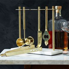 Bring back the glamour of 1950s cocktail hour with the Deco Barware Collection | double jigger, fruit knife, tongs and bottle opener - stainless steel gold-finished bar tools with a solid marble base, W23 x D10 x H24cm