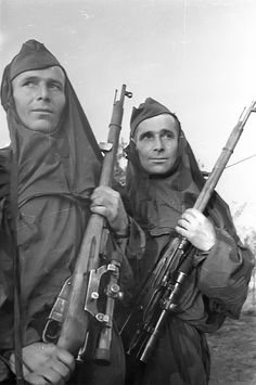 "Red Army snipers wearing the forest camouflage wrap-around that was issued in early 1943. Original caption refers simply to ""Soviet snipers."" Undated. Note the Moshin-Nagant rifles with the modified PEM scope.To this day, the M-N remains the most widely produced and longest serving sniper rifle in the world, and remained the Soviet Union's main sniper rifle until it was superseded in 1962 by the semi-automatic SVD Dragunov rifle."