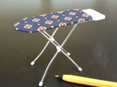 A 1/12th scale ironing board. ( Designs and colours of cover will vary)
