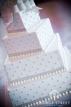 Tiered square cake, white, bow on top, silver dots, silver ribbon and icing dots on bottom of each layer