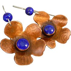 Copper And Lapis Flower Earrings Beautiful and feminine Copper flowers that I cut, textured in a floral pattern, and soldered together with a 6mm Lapis cabochon center. The earrings measure approx 2 inches from the top of my sterling silver and Lapis ear wires.