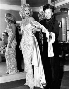 Some outfit? Marilyn Monroe puts o her long white gloves for the premiere of How To Marry A Millionaire, 1953.
