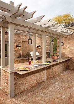 This modern outdoor kitchen has a beautiful design. The bricks suit the whole decor beautifully.