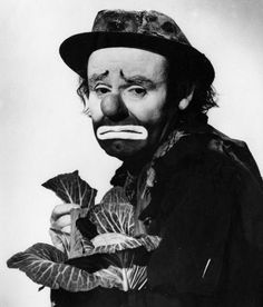 Portrait of Ringling Circus clown Emmett Kelly holding a cabbage head.