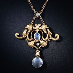 Art Nouveau Moonstone Necklace - A simply stunning Art Nouveau pendant necklace, circa 1900, aglow with a pair of shimmering moonstones (the center moonstone is as blue as we've ever seen), plus a pair of sparkling diamonds and a pair of shimmering seed pearls. Flowing golden leaves and scrolls with a rich, warm patina comprise the main section of this dreamy turn-of-the-century jewel.