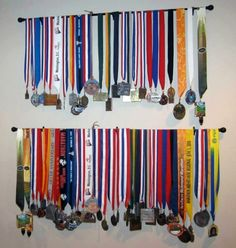 Use a curtain rod to display medals.  Neat idea.  Perhaps it could be under a shelf and then put trophies on top. Might work for all those swim medals!