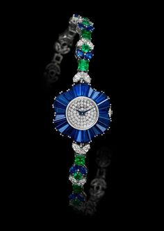 Fleur Watch from Delicate Collection by De Laneau.  White gold case set with 24 baguette-cut blue sapphires. Dial set with 70 diamonds. Mechanical movement. Bracelet set with 24 navette-cut diamonds, 20 navette-cut blue sapphire, 11 princess-cut emeralds and 10 emeralds . White gold clasp.