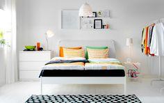 침대와 오렌지/그린색 침구, 조명 일체형 보조테이블, 서랍장이 있는 화이트 톤 침실