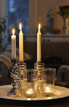 Adore the use of a fun drinking glass with a tealight candle, perfectly mixed with the taper candles and holders
