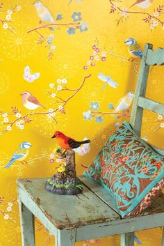 Shabby chic chair and bird vignette against yellow-vintage wall paper.