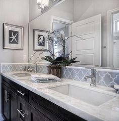 dark cabinets, light gray walls, white counters, grey back splash