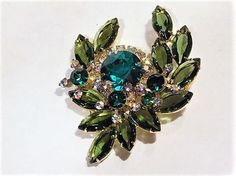 ITEM # 011704 (B-42)   Beautiful verified DeLizza  Elster aka Juliana glass layered and dimensional rhinestone brooch.   Brooch consists of a large deep emerald green faceted round open back rhinestone, unable to count the aurora borealis accent rhinestones surrounding the center stone as they, at one point, go underneath one of the florets. There are three florets, each consisting of the same deep emerald green faceted glass round rhinestone that are the only rhinestones in this brooch not…