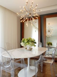love the height of everything: the white window treatments, the mirrors, with dark grey walls, ghost chairs, white marble table