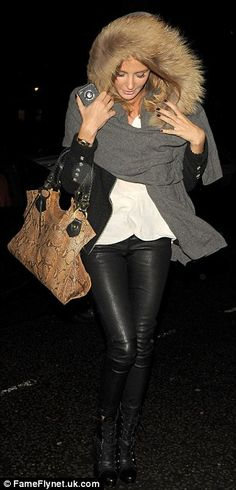 Stormy night: Millie made a fashionable entrance as she fought the wind off in a fur hooded shawl