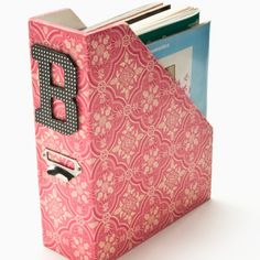 Cover magazine holders with fabric and stick a letter on them for cute organized storage!