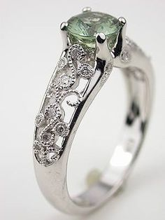 Green Sapphire Engagement Ring, RG-2813p....18k white gold.      Scroll down for pictures and detailsGreen Sapphire Engagement Ring  A green sapphire is set at the top of a delicate vine of diamonds in this unusual engagement ring. The renewing hope of spring comes to life with this engagement