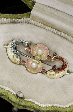 "An Art Nouveau enamel and pearl brooch, by Alfred Phillips, circa 1895. The two pink enamel scallop shells, each centred with a 3.2mm pearl, between two leaping fish set with blue, red and white enamel, maker""s mark AP.:"