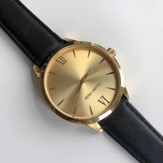 Classic round women's watch with gold mirrored face and black leather watch strap made from high-quality leather scraps that would otherwise go to waste. BERG + BETTS watches are ethically made and hand assembled in Canada. Leather Scraps, Black Leather Watch, Stainless Steel Case, Mindful, Quartz, Watches, Band, Accessories, Collection