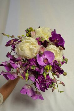 Unique white and magenta bridal bouquet with peonies, orchids, stock, and lisianthus. Fleurish Floral Designs