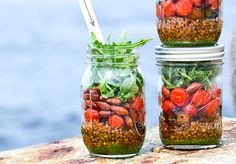 A beautiful mason jar recipe for a vegan wheat berry salad with basil-almond pesto, sautéed eggplant, blistered tomatoes and arugula from @FloatingKitch