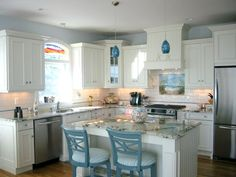 Teal lights and chairs, white kitchen. Beach Kitchen