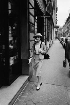Coco Chanel walks right by her store in Paris.