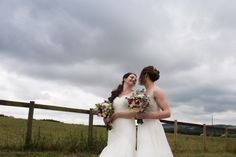 portrait of two brides with dramatic stormy skies