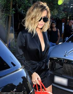 Classy: Khloe styled her short blonde locks loose with waves, opting for a center part...