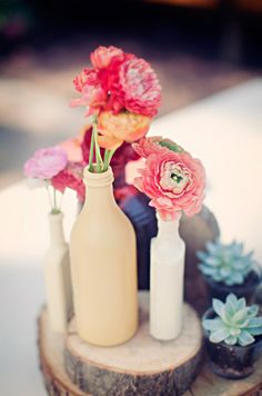 Just some bottles and some spray paint!  love this - a) cuts down on flower costs, b) love the wood slab, c) little succulents!